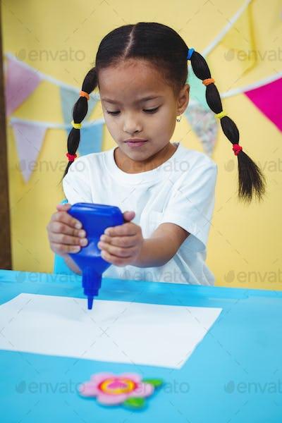 Girl holding a bottle of glue at her desk