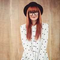 Smiling hipster woman holding book belt against wooden background