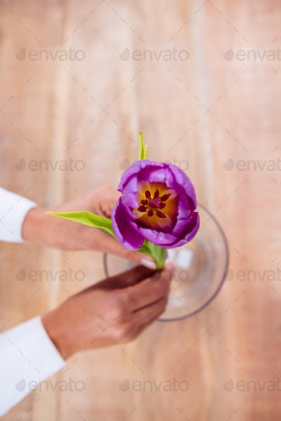 Woman putting a flower in a vase on wooden desk