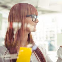 Attractive hipster woman looking at sticky notes in her office