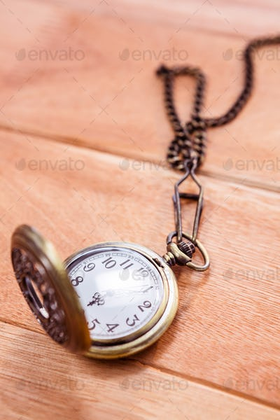 Close up view of a pocket watch on wooden desk