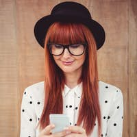 Smiling hipster woman using her smartphone against wooden background