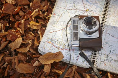 Still life in the autumn forest with camera and map. Travel