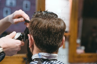 Barbers hands making haircut to man using trimmer