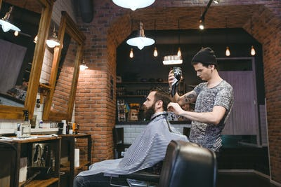 Young hairdresser drying man's hair with blowdryer