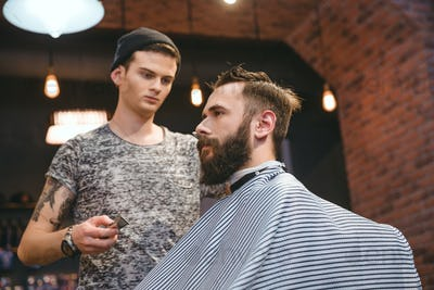 Concentrated hairdresser making haircut to bearded handsome man at barbershop