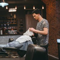 Barber finishing grooming and taking care of client's face