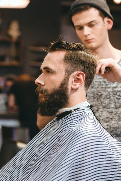 Professional hairdresser cutting bearded man's hair