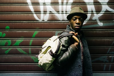 Half length of young handsome afro black man holding a bag, lean