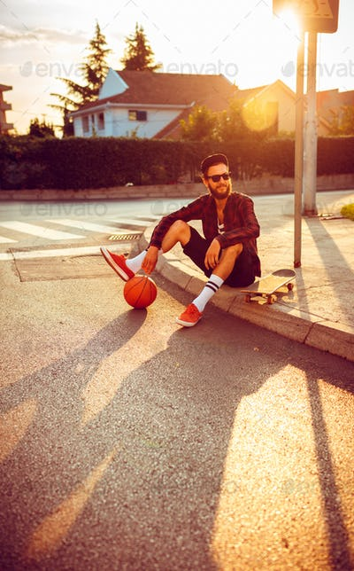 Man in sunglasses with a basketball and skateboard sitting on a