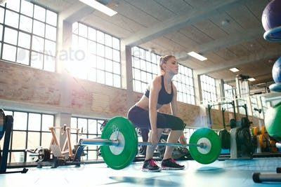 Female athlete lifting weights in health club.