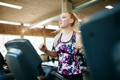 Young female running on treadmill in health club