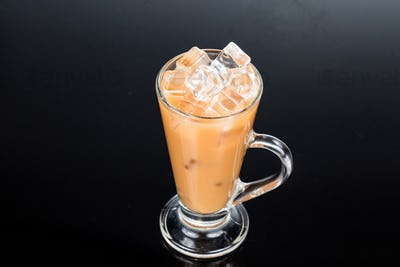 Refreshing ice cold tea with milk in transparent glass