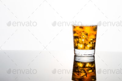 Refreshing iced tea in transparent glass with white background