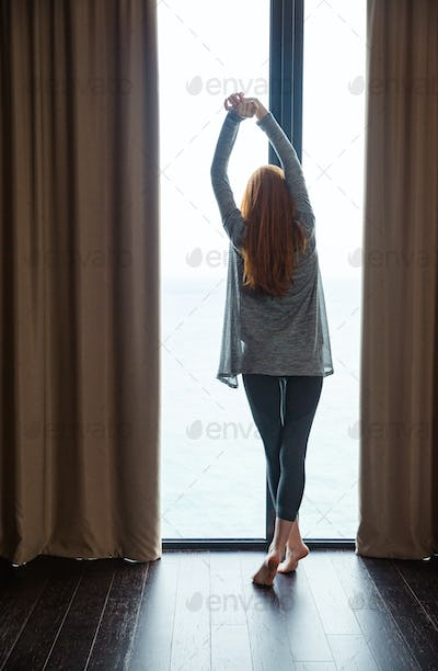 Attractive slim lady standing and stretching at the big window