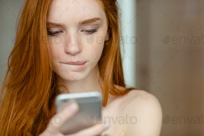 Beautiful redhead woman using smartphone