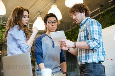 Smart  man sharing his ideas with concentrated coworkers