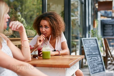 Female friends meeting at sidewalk cafe