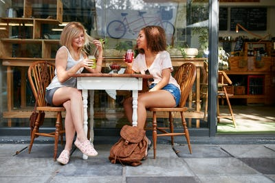 Two happy women at cafe enjoying drinks and chat