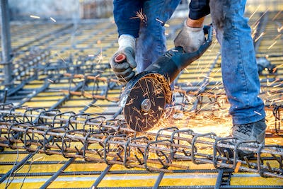construction industry details - worker cutting steel bars using angle grinder mitre saw.