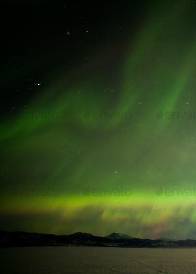 Northern Lights dancing over frozen Lake Laberge Yukon Canada