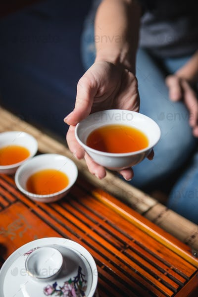 Female hands holding cup with tea