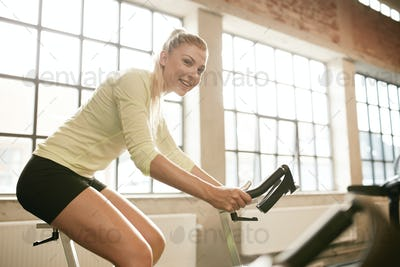 Sportive woman working out on exercise bike
