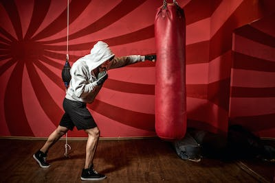 professional boxer training at gym, practicing kicks and punches