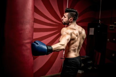 professional boxer fighting and training in gym. Strong, muscular man training and boxing