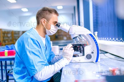 Male scientist, chemist working with microscope in pharmaceutica