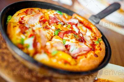 Close-up of hot pizza with fresh ingredients and vegetables served on hot plate