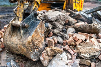 close-up of excavator bucket loading rocks, stones, earth and concrete bricks