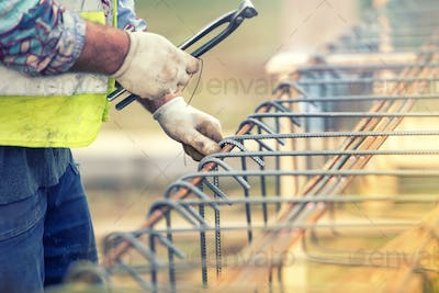 worker hands using steel wire and pliers to secure bars on construction site and preparing
