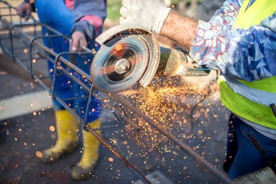 industrial engineer working on cutting a metal and steel bar with angle grinder