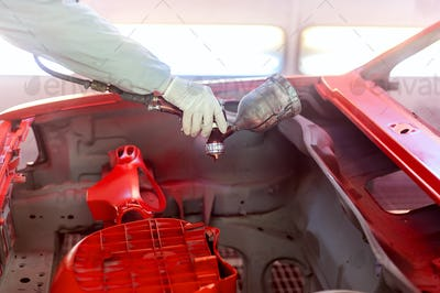 worker painting a car element, the hood with special paint and tools