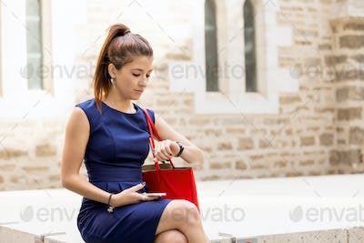 Pretty business woman looking at her watch
