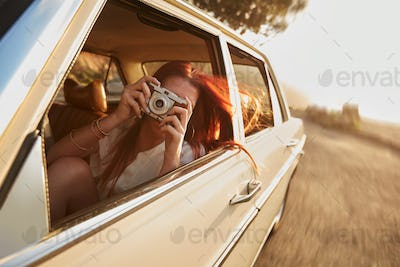 Female capturing a perfect road trip moment.