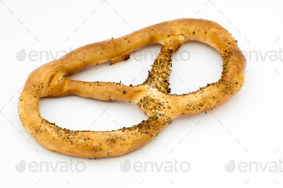 close-up of one pretzel, brown and covered with poppy seeds, on a white background