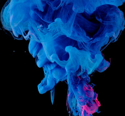 Blue pink clouds of ink in liquid isolated on black