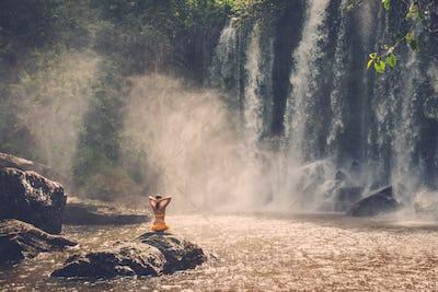 Beautiful woman sitting near waterfall enjoying the sun, Phnom Koulen at Siem Reap, Cambodia