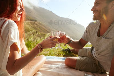 Cheerful young couple on picnic drinking wine