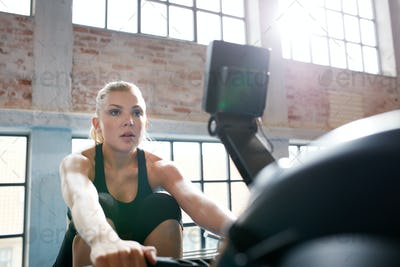 Female working out on a rowing machine at the gym