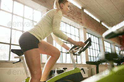 Female exercising on a bike in gym
