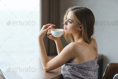 Attractive sensual woman sitting at the table and drinking coffee