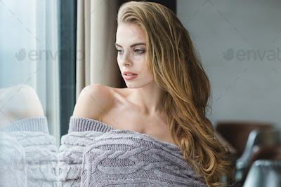 Portrait of seductive blonde female wrapped in grey knitted coverlet