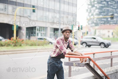 Knee figure of young handsome afro black man leaning against an