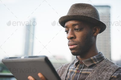 Portrait of young handsome afro black man using a tablet, lookin