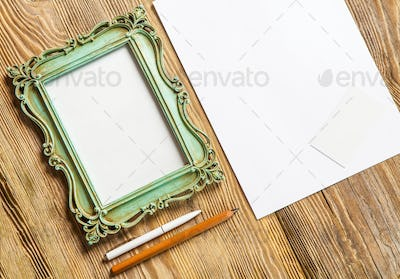 The mockup on wooden background with vintage old picture frame