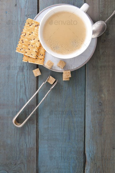 Cup of coffee and sugar on old wooden boards.