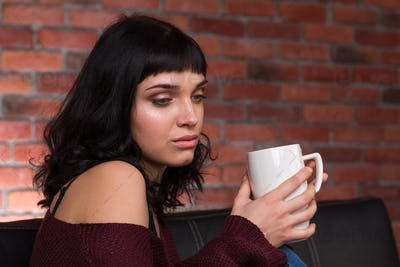 Beautiful young woman sitting on sofa and drinking coffee
